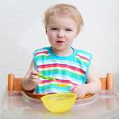 Girl wearing colorful bib eating porridge — Stock Photo