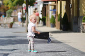 Cute baby girl standing or walking in the middle of the street in outlet village during sales with black shopping bag in her hands, crowd of people in the background — Stock Photo