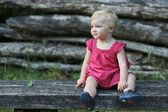 Baby girl sitting on a wooden bench — Stock Photo