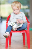 Baby girl sitting indoors on a small red plastic chair — Stock Photo