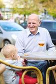 äldre man sitter med sina barnbarn i staden — Stockfoto