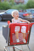 Baby girl sitting in red shopping cart outside of a hypermarket — ストック写真