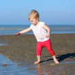 Girl plays with watering can on beach — Stock Photo