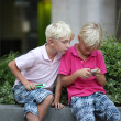 Brothers playing together games with touchscreen smart phones — Stock Photo