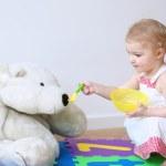 Girl feeding her big white teddy bear with porridge from spoon — Stock Photo