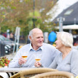 Couple of seniors enjoying glass of cold beer — Stok fotoğraf