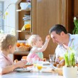 Father with teenager son and toddler daughter eating eggs during family breakfast on Easter day sitting together in sunny kitchen. Selective focus on girl and man. — Stock Photo