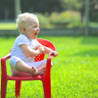 Baby girl sitting on a small red chair in a garden — Stock Photo #42670253
