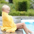 Boy sitting at the edge of outdoor swimming pool — Stock Photo