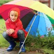 Постер, плакат: Boy hiding from rain sitting under umbrella