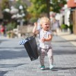 Cute baby girl standing or walking in the middle of the street in outlet village during sales with black shopping bag in her hands, crowd of people in the background — Stock Photo #42670377