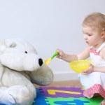Girl feeding her teddy bear with porridge from spoon — Stock Photo