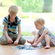 Постер, плакат: Girl playing puzzles with her brother