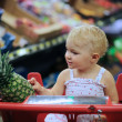 Baby girl sitting in red shopping cart at supermarket — Stock Photo #42670601