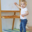 Baby girl draws with crayon on a white board — Stock Photo #42670889