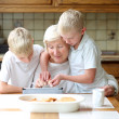 Twin brothers teaching grandmother to play on tablet pc — Stock Photo