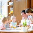 Family of five: father, mother and three kids, teenager sons and toddler daughter eating eggs during family breakfast on Easter day sitting together in sunny kitchen. Selective focus on little girl. — Photo #42670965