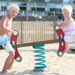 Boy and baby sister rocking on a spring seesaw swing — Stock Photo