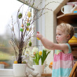 Adorable little blonde toddler girl decorating with Easter eggs cherry tree branches standing in the kitchen next a window with garden view — Stock Photo