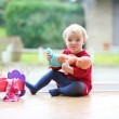 Girl playing with doll sitting on the tiles floor — Stock Photo