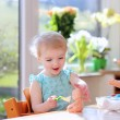 Girl feeding with yogurt her dolls — Stock Photo
