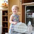 Smiling blonde toddler girl helping in the kitchen taking plates out of dish washing machine — Stock Photo