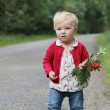 Baby girl walking on a road along autumn forest — Stock Photo