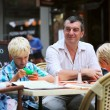 Father with three children are having fun in cafe — Stock Photo