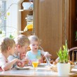 Group of three kids, twin brothers with their little toddler sister, eating eggs during family breakfast on Easter day sitting together in sunny kitchen. Selective focus on little girl. — Stock Photo #42671867