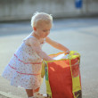 Baby girl inside big shopping back full of food products — Stock Photo