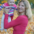 Mother and her baby daughter playing in an autumn park — Stock Photo