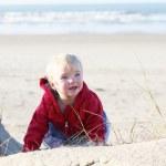 Baby girl crawls to the dunes along beach — Stock Photo