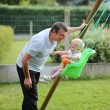 Happy father with his adorable baby daughter playing with swing in the garden at backyard of the house — Stock Photo