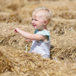 Baby girl playing with straw — Stock Photo
