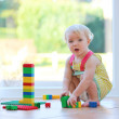 Girl playing with plastic blocks sitting on the tiles floor — Stock Photo #42672191