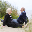 Senior couple sitting in the dunes — Stock Photo