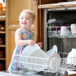 Girl taking plates out of dish washing machine — Stock Photo