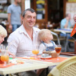 Family in cafe on summer terrace in a center of busy city street — Stock Photo #42672255
