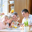 Family of five: father, mother and three kids, teenager sons and toddler daughter eating eggs during family breakfast on Easter day sitting together in sunny kitchen. Selective focus on little girl. — Stock Photo