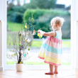 Cheerful blonde little toddler girl decorating cherry tree branches with Easter eggs standing indoors next to a big window with street view — Stock Photo