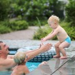 Father playing with children in outdoors swimming pool — Stock Photo