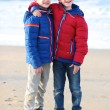 Brothers in warm colorful coats standing on the beach — Stock fotografie