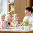 Father with three kids, teenager sons and toddler daughter eating eggs during family breakfast on Easter day sitting together in sunny kitchen. Selective focus on little girl. — Stock Photo