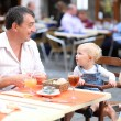 Father with children relaxing in cafe — Stock Photo