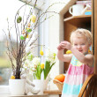 Adorable little blonde toddler girl decorating with Easter eggs cherry tree branches standing in the kitchen next a window with garden view — Stock Photo #42672639