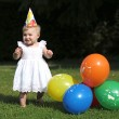Baby girl next to colorful balloons — Stock Photo #42673315