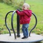Baby girl riding on merry-go-round carousel — Stock Photo #42673341