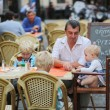 Father with three children in cafe — Stock Photo