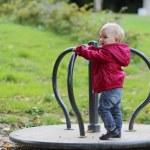 Baby girl riding on merry-go-round carousel — Stock Photo #42673425