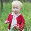 Baby girl holding small rowan branch in her hand — Stock Photo
